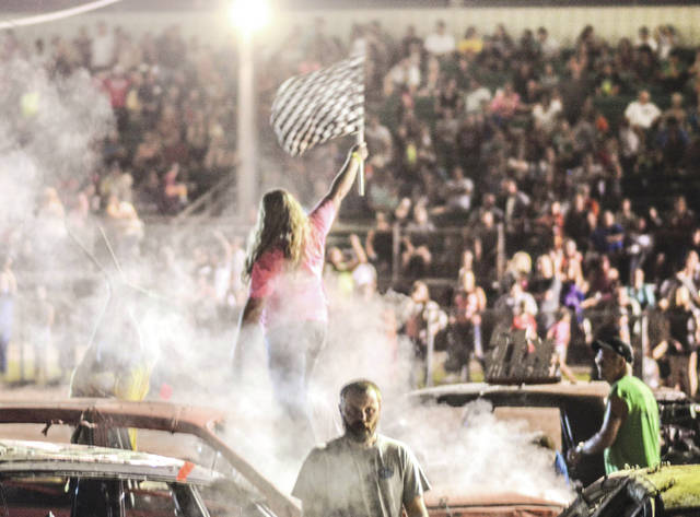 """Cassie Storer of Xenia stands on the hood of her car and waves the checkered flag to the Greene County Fair grandstand crowd, after Monday's July 31 Smash It Demolition Derby. With her friends chanting """"Cassie! Cassie! Cassie!"""" Storer won the Street Stocks competition."""