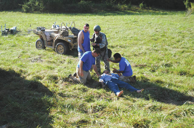 "Tech Warrior Exercise participants helping a ""victim"" of a wreck. The victim is actually a test dummy that is able to make sounds and pump liquids throughout its shell which enables the dummy to have a ""squirting"" effect if needed."