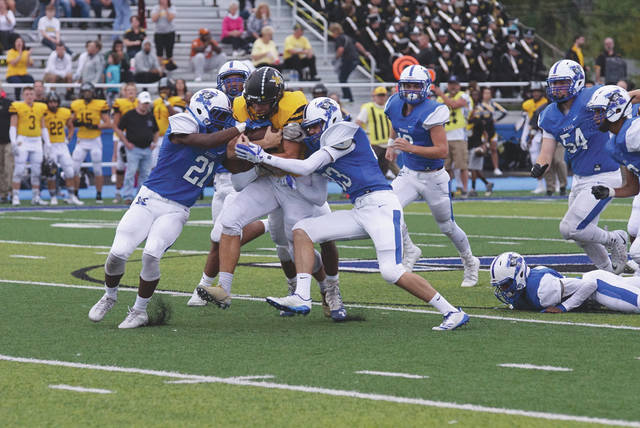 Isaiah Bowser drags a bunch of Xenia Buccaneers along for a big gain, during the first half of Friday's high school football game at Doug Adams Stadium in Xenia. In three quarters of play, Bowser had gained 324 yards and the Sidney Yellow Jackets had a 42-35 lead.