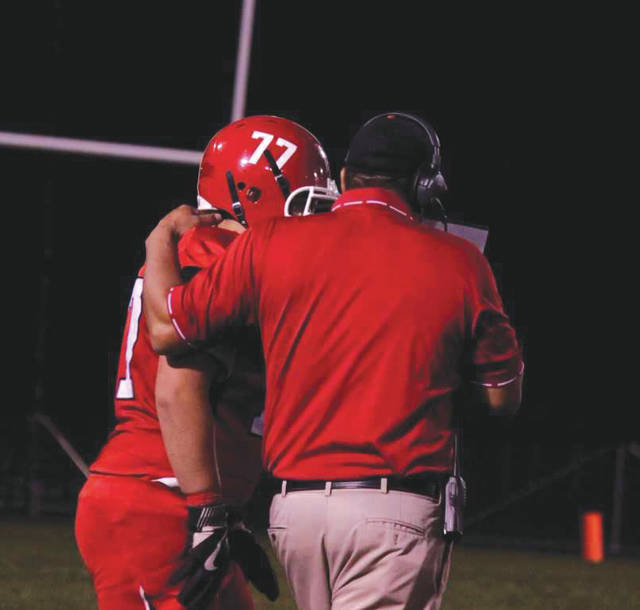 Junior lineman Chandler Flores goes over a play with Head Coach Jason Christian before heading back out onto the field, Friday, Oct. 20 in a narrow 7-6 home loss to Greenon.