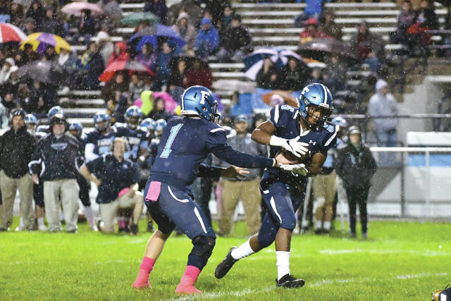 Senior running back K.J. Redmon (5) takes a handoff from quarterback Wesley Watts (1) in the first half of Friday's Oct. 27 high school football game at Memorial Stadium in Fairborn. The host Skyhawks won the Greater Western Ohio Conference game, 20-14.