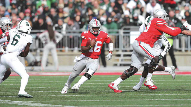 Ohio State four-year starter at quarterback J.T. Barrett runs with the ball during a 48-3 win over Michigan State. He is going for his fourth straight win against Michigan, on Saturday, Nov. 25 in Ann Arbor, Mich.