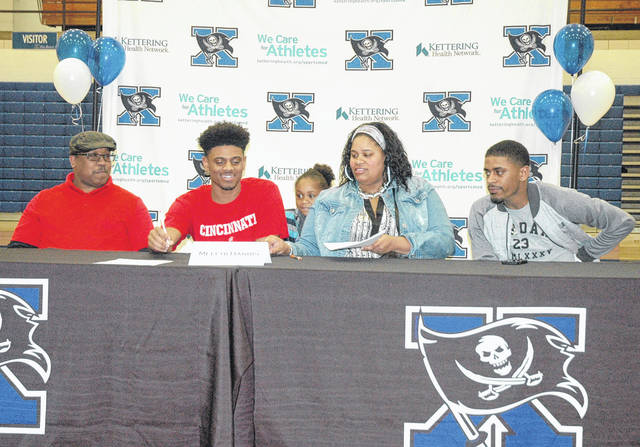 Scott Halasz | Xenia Daily Gazette Xenia senior Meechi Harris signs a National Letter of Intent to play football at the University of Cincinnati next year. Harris, a wide receiver and return specialist, had been committed to Kentucky, but de-committed earlier in the week and announced his choice Dec. 20 in the school gym. Harris said it was hard to dec-ommit but he liked the atmosphere at UC better than UK.