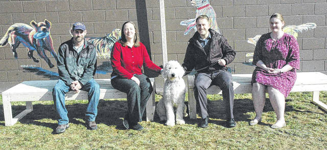 Scott Halasz | Greene County News Wright State MBA students Mark Preston, Angela Hart, Tony Hermes, and Ericka Thomas sit on new benches made for Xenia-based 4 Paws for Ability as part of their project. They are pictured with Hamlet.