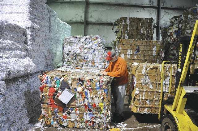 Submitted photo Roger Smart records the tonnage for recycled bales of paper stacked high inside the Base Recycling Center.