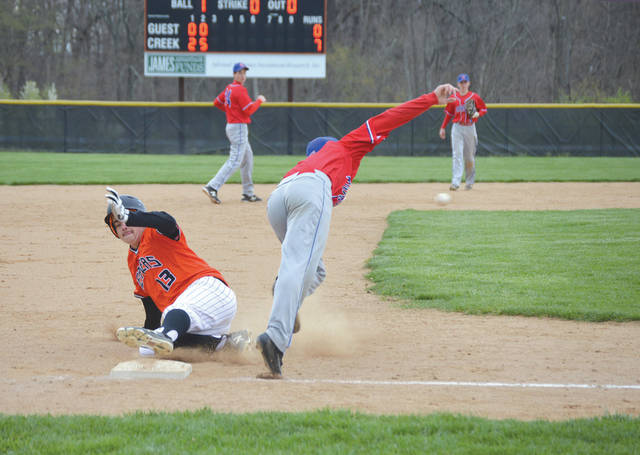 Beavercreek's Clay Cash (13) slides safely into third base as Carroll's Jacob Maurer lunges after a wild throw on April 28. The ball sailed into left field and Cash scored on the play, part of a six-run second inning for the host Beavers.