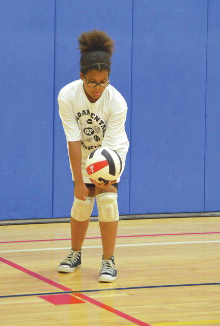 A Xenia U-12 youth volleyball player concentrates on hitting an underhanded serve, during YMCA Greater Dayton Spring Volleyball league action, May 24 at the Fairborn YMCA.