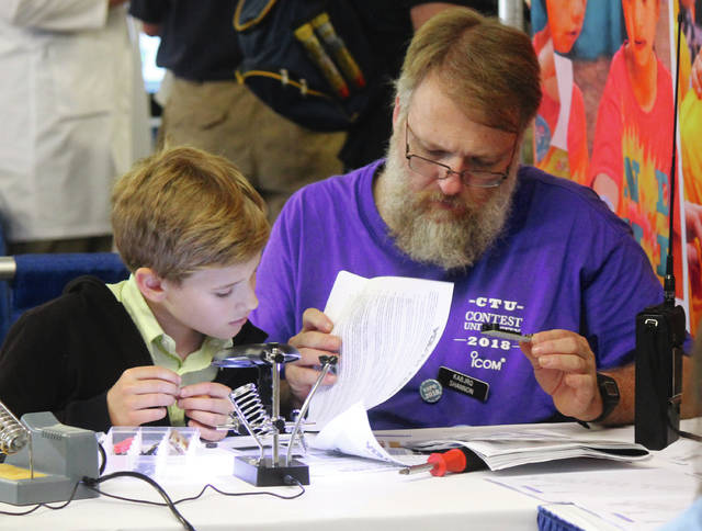 Anna Bolton | Greene County News Aaron Latham and his father Shannon Latham build a kit together at the Youth Tech area of Hamvention May 18 at the Greene County Fairgrounds.