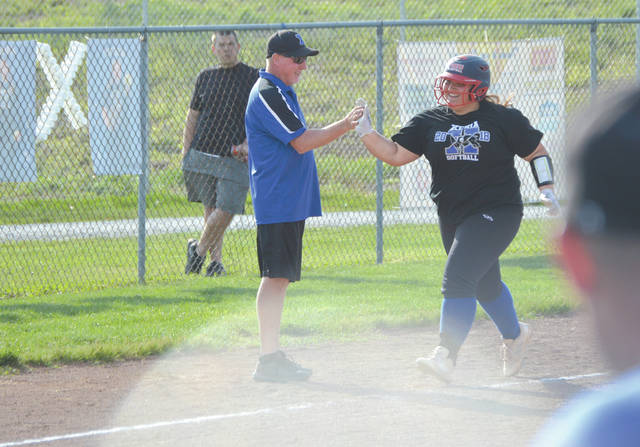 Xenia girls softball coach John Miner congratulates Caity Moody as she rounds third base after hitting a line drive home run over the left field fence in the third inning of a Division I sectional high school softball tournament game, May 9 with visiting Tecumseh.