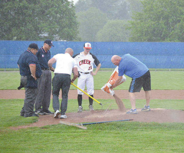 Beavercreek pitcher Brandon DeWitt and the game umpires look on as Xenia High School Athletic Director Nathan Kopp and XHS baseball coach Barry Claus apply Speedy Dry to the pitcher's mound, Thursday May 17 during a rain delay of the Division I baseball sectional final game between Beavercreek and Centerville.