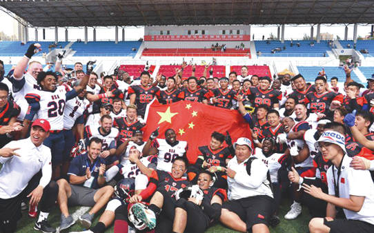 Members of Team USA Football and the Chinese national team celebrate together after a recent June 15 game between the two at the World University Championships of American Football in Harbin District, China at Harbin University Commerce Stadium.