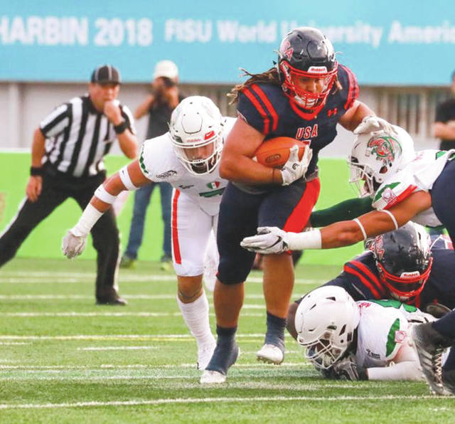 A Team USA Football running back gets through a hole on the right side of the Mexico defense, June 21, in a World University Championship of American Football tournament game in Harbin District, China. Defending champion Mexico rallied to claim a 19-17 win.