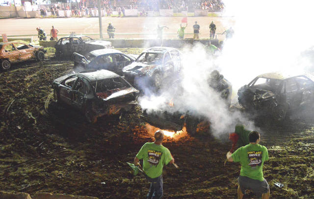 Smash It Demolition Derby and New Jasper Fire Department officials react as Xenia's Tony Jenkins climbs out of his burning car, July 30 during the Street Mini division competition at the Greene County Fair. Jenkins was unharmed in the incident and finished third. Xenia's Matthew Reed won the 25-car event.