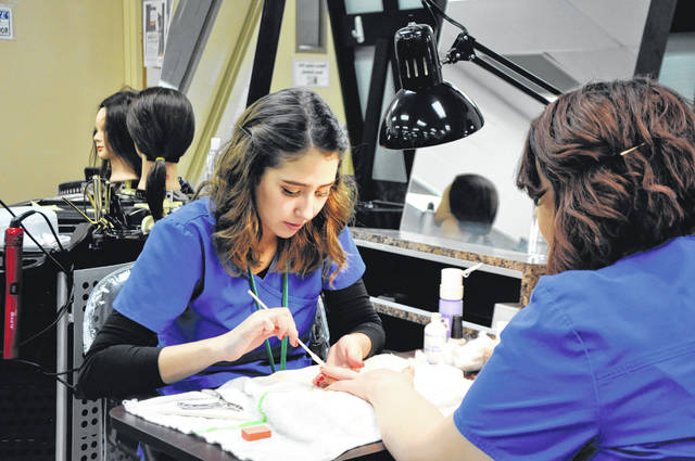 Submitted photo Greene County Career Center students find out quickly that hands-on learning is part of their school experience each day. Natalie Maldonado of Fairborn practices nail care with fellow cosmetology senior Tyler Gorman from Xenia. Cosmetology students earn the needed hours to take the State Board of Cosmetology and Barber exam at the end of their senior year. GCCC allows them to save thousands of dollars in tuition and enter the workforce immediately following graduation from high school.
