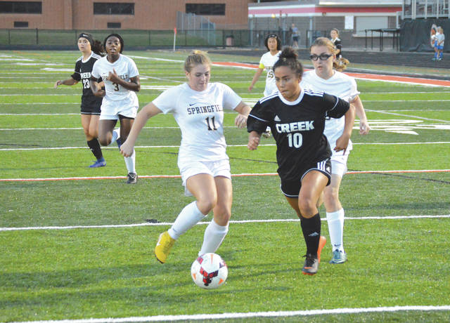 Beavercreek junior midfielder Diana Benigno (10) drives past Springfield's Maddie Cochran and Annmeri Turner for a first-half goal, Sept. 19, at Frank Zink Field. Beavercreek remains undefeated after Wednesday night's 9-0 win.