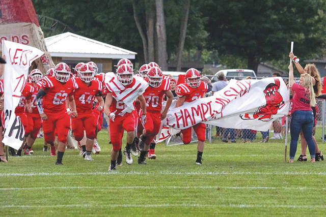 Cedarville High School football players charge through a pre-game banner on homecoming, Sept. 21 in Cedarville.
