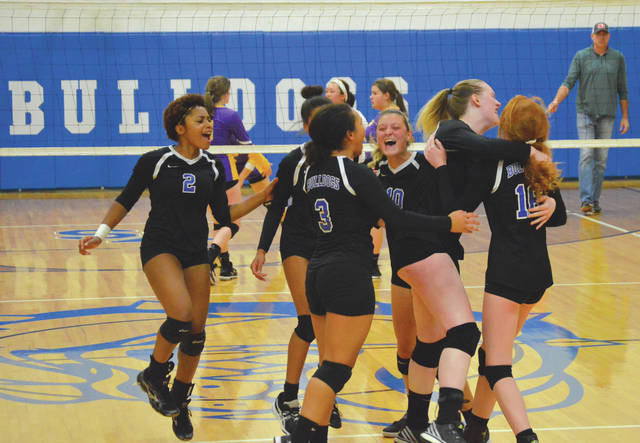 Yellow Springs girls volleyball players Annlyn Foster (2), Angelina Smith (behind 3), Aaliya Longshaw (3), Tyler Linkhart (10), Alex Ronnebaum and Emma Ronnebaum (16) celebrate moments after defeating rival Emmanuel Christian in three sets, Sept. 27 at Yellow Springs High School.