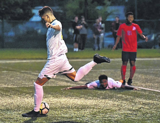 Submitted photo Alec Philippe watches from the turf as his pass gives Deri Corfe a wide open net for the Raiders second goal of the match, Sept. 25 against visiting Duquesne University.