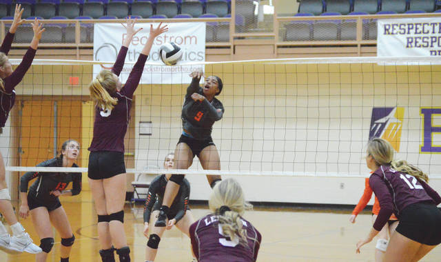 Beavercreek senior hitter Kirsten Williams (9) hits past the block try of Lebanon's Lucy Kirkwood, Oct. 24 in a girls high school volleyball sectional final in Vandalia.