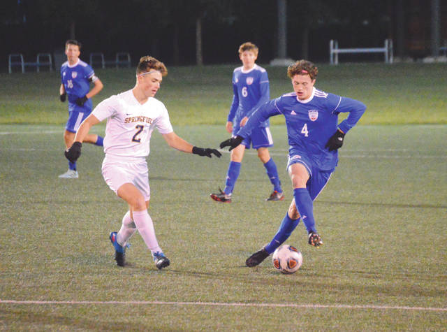 Patriots sophomore Conner Bailey (4) cross dribbles around Springfield senior midfielder Braedan Carey, in the first half of an Oct. 18 Division I sectional tournament boys high school soccer match at Wright State University's Alumni Field in Fairborn. Carroll won the match, 4-0.