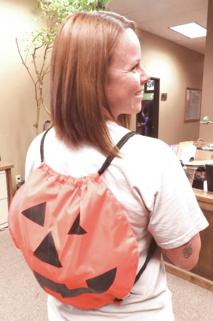 GCP&T Fiscal Support Technician Callie Dodge shows off one of the pumpkin sling bags that will be given to the first 100 who attend each night.