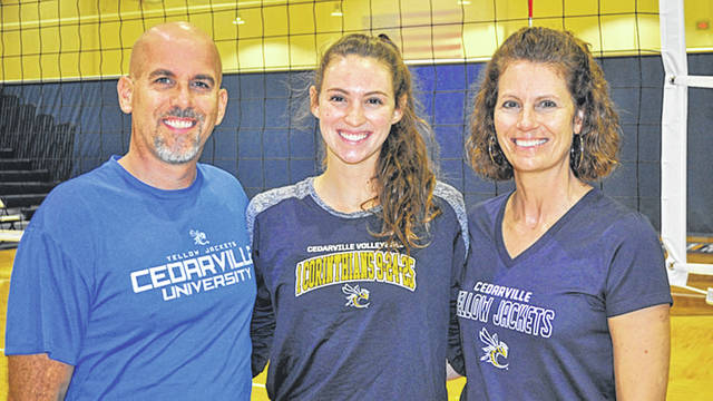 Submitted photo Cedadrville University women's volleyball senior Taylor Wilkerson (center) is joined by her parents, Mike and Christy Wilkerson, prior to a home match.