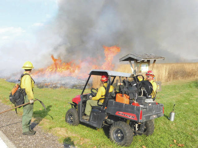 Submitted photo Darryn Warner, Natural Resources Program Manager, right, and personnel from the U.S. Fish and Wildlife Service Big Oaks Wildlife Refuge monitor a prescribed burn at the Huffman Prairie in 2016.