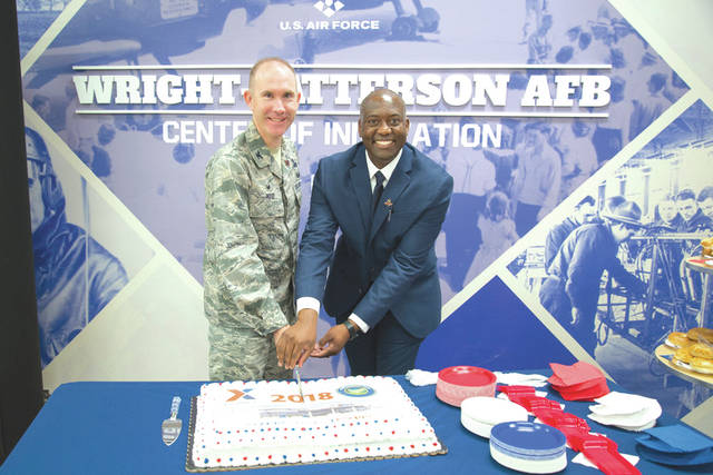 Submitted photo Col. Leonard T. Rose, 88th Mission Support Group commander, and Jermaine Wilson, Wright-Patterson Exchange general manager, cut a commemorative cake at the Exchange's grand re-opening ceremony.