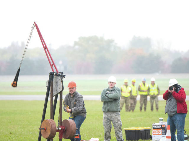Submitted photos An Air Force Life Cycle Management Center's F-15 Engineering Branch team member pulls the trigger on their trebuchet-style catapult to hurl a small pumpkin during the 14th annual Wright-Patterson Air Force Base, Ohio, pumpkin chuck Nov. 2. Representatives from the 88th Air Base Wing safety office watch in the background.