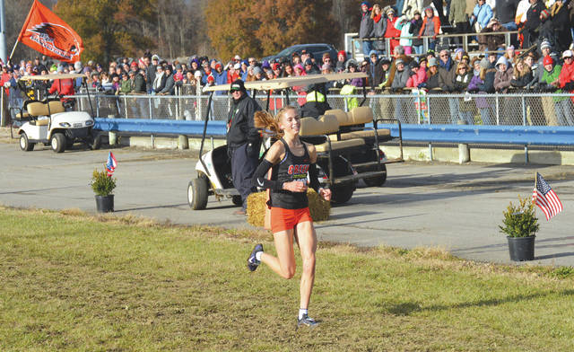 With the Beavercreek High School banner waving and all eyes upon her, junior Taylor Ewert smiles as she heads to the finish line to win the girls Division I state cross country individual title, Nov. 10, at National Trail Raceway in Hebron.