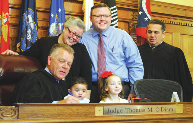 Whitney Vickers | Greene County News The Watkins family — Emily, Andrew, 4-year-old Claire and 6-month-old Clayton — as Greene County Probate Judge Thomas O'Diam signs paperwork during Clayton's adoption hearing. Judge Adolfo Tornichio, juvenile court judge, sat in on the hearing as adoption cases start in the juvenile court.