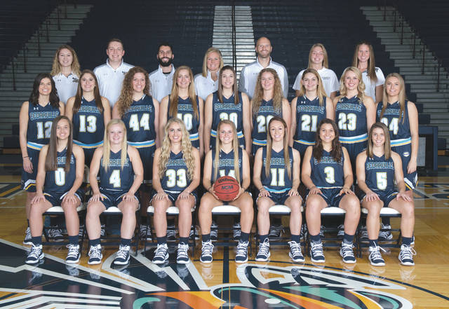 Members of the 2018-19 Cedarville University women's basketball team are (seated left-to-right) Emily Chapman, Baylee Bennett, Ellie Juengel, Kelly Poole, Regina Hochstetler, Abby Wolford, Ashlyn Huffman. (Middle row) Anna DeFilippo, Stevie Johnting, Lexi Moore, Victoria Fliehman, Alli Roh, Isabelle Bolender, Annabelle Hinds, Cameron Peek, Allison Mader. (Back row) Student Assistant Shannon Fish, Assistant Coach Stephen Buettell, Assistant Coach John Leonzo, Head Coach Kari Hoffman, Assistant Coach Jimmy Hoffman, Student Athletic Trainer Alyssa Nusser, Assistant Athletic Trainer Becca Stokes.