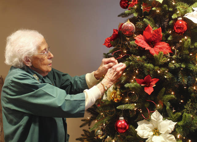 "Anna Bolton | Greene County News Volunteer Frieda Parks hangs an ornament on the ""Tree of Lights"" in the Greene Memorial Hospital lobby. The ornaments honor community members by name and raise funds for the hospital."