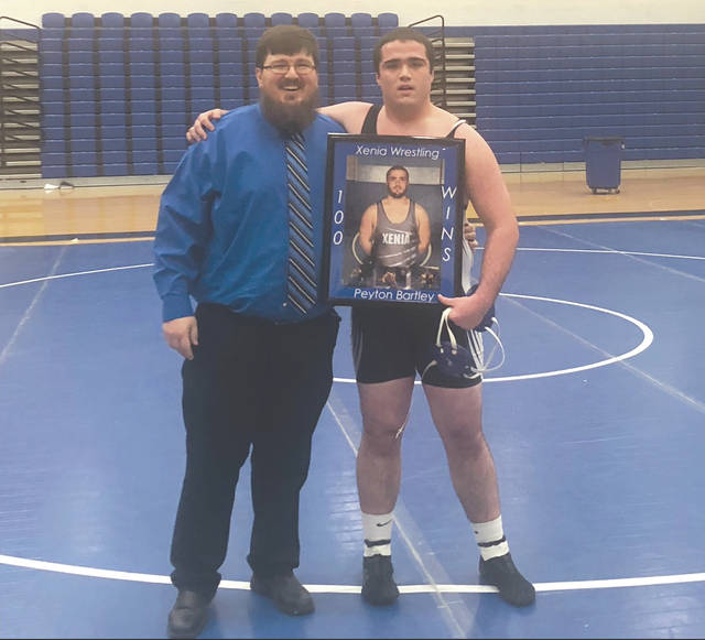 Xenia High School's Peyton Bartley (shown with Buccaneers head coach Sean Schooley), recently won his 99th and 100th career wrestling matches. The Bucs heavyweight currently leads the Greene County area with an 8-1 overall record with six pins.