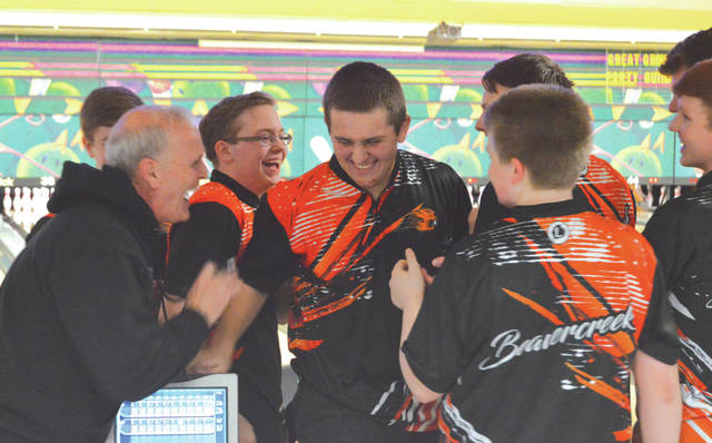 Senior Grant Reeve (center) shares a laugh with coach Bob Bobbitt (left) and the rest of the varsity boys team after tossing a 299 first game, Jan. 15, in a high school bowling match against Wayne, at Beaver-Vu Lanes in Beavercreek.