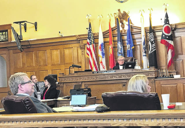 Anna Bolton | Greene County News Defense Attorney Peter Certo and defendant Kathy Smith turn to look at a photo marked as evidence Jan. 28 during trial as Ohio State Highway Patrol Trooper Jaysen Kelly testifies. Judge Stephen Wolaver looks on.