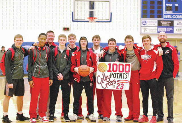 Cedarville junior Colby Cross (holding the ball) poses with his teammates and coaches after scoring his 1,000th career point in dramatic fashion, a 51-50 Indians win over Franklin Monroe, Jan. 26 in Arcanum. Cross has now scored the winning basket in the last two Cedarville boys high school basketball games. The Indians have now won five of their last seven games and are currently second in the Ohio Heritage Conference's South division.