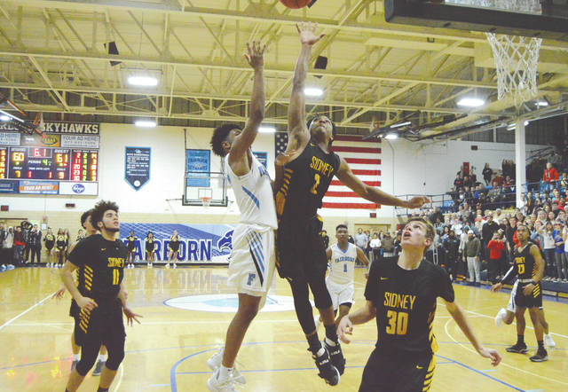 Fairborn's Shaunn Monroe shoots over Sidney defender Ratez Roberts' block attempt for the go-ahead score in the Skyhawks' come-from-behind 63-61 win, Jan. 18 in the Baker Memorial Field House.