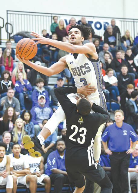 Xenia's Zack Gaither (3) scores and draws a foul on Isaiah Hoyt of First Love Christian Academy, during third-quarter action at the annual Flyin' To The Hoop basketball showcase event, Jan. 19 at Kettering's Trent Arena.