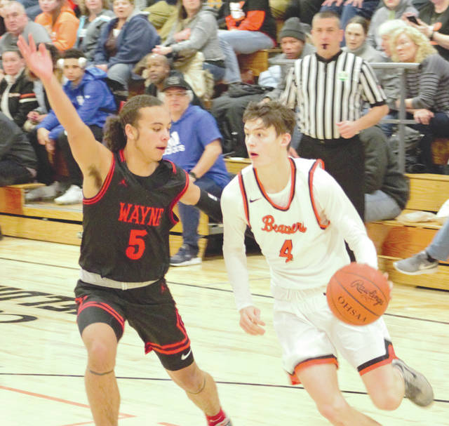 Beavercreek senior Brayden Walther (4) drives in from the corner for a layup against Wayne sophomore Malcolm Curry in their Greater Western Ohio Conference divisional matchup Feb. 1 in Beavercreek.