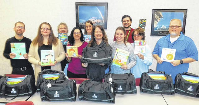 Photos courtesy Greene County Children Services Jana Gruber (center), executive director and founder of Books to the Rescue, with several staff members of Greene County Children Services donates 76 bookbags to the agency.
