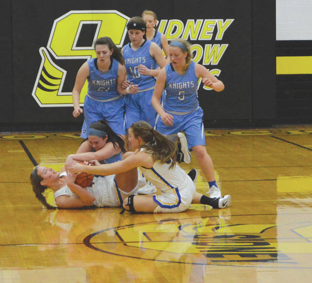 Legacy Christian's Maddy Combs wrestles for a loose ball with Russia's Laurissa Poling and Jenna Cordonnier, as LCA teammates Kathleen Ahner (21), Emily Riddle (10) and Margaret Kensinger (5) close in from behind, during Wednesday's Division IV district semifinal game at Sidney High School.