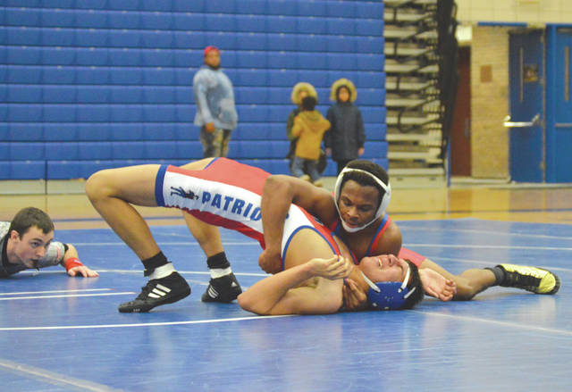 Xenia's Desmond Diggs (top) hangs on as Carroll wrestler Bryan Quiroz fights to keep from being pinned, in the second period of Friday's Feb. 1 132-pound match. Diggs won by technical fall, 17-2.