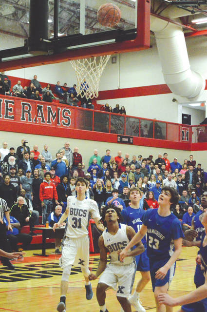Xenia's Dylan Hoosier (center), teammate Noah Crawford, Miamisburg teammates Alex Ball and Brett Hensley, and a near-capacity crowd look on as Hoosier's winning shot falls through the hoop to give the Xenia Buccaneers a 74-72 overtime win, Feb. 26 at Trotwood-Madison High School.
