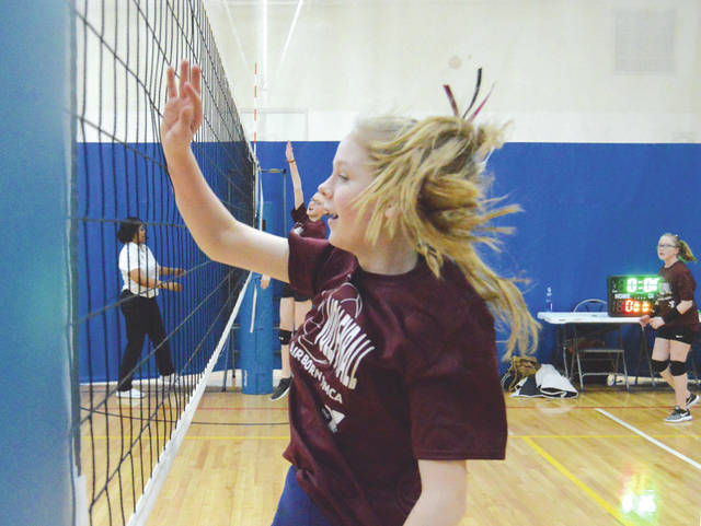 Two members of the Maroon team partake in a net drill prior to a girls volleyball match Feb. 14 at the Fairborn YMCA.