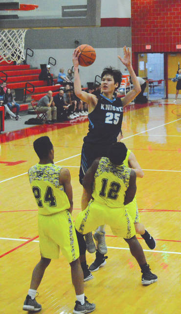Legacy Christian's Mike Sharavjamts (25) drives in for a score, during first-half action Feb. 22 at Troy High School. East Dayton Christian's Kendall Holt (12) was called for a foul on the play.