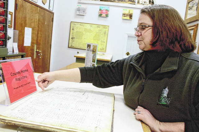 Greene County Archivist Robin Heise reads a line from registers from the county home, formerly known as the Greene County Infirmary.