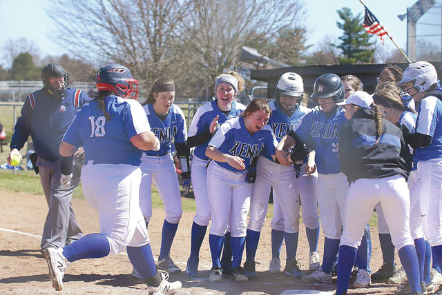 Members of the Xenia High School softball team greet Caity Moody at home plate after she hit a home run March 23 against visiting Pleasant Hill Newton.