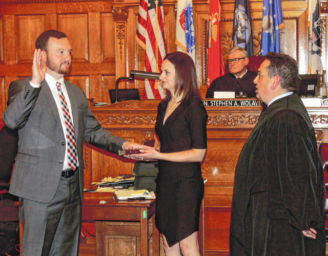 Anna Bolton | Greene County News Judge Adolfo Tornichio presents the oath of office to Greene County Treasurer Kraig A. Hagler, alongside his wife Christina Hagler, March 29 in Greene County Common Pleas Court. Greene County Republican Central Committee appointed Hagler Jan. 24 to fill the vacancy left by Commissioner Dick Gould.