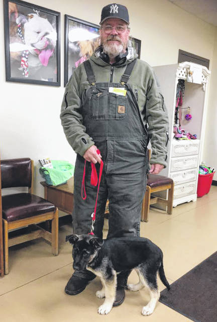 Photo courtesy GCAC Paul Charles gets ready to take his new puppy, Yankee, home March 21 after waiting outside Greene County Animal Care & Control for 16 hours in the rain.